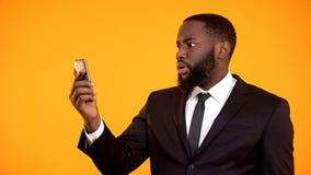 Manlig l?sande email f?r chockad afrikansk amerikan p? telefonen, mobil app, h?pnad royaltyfri foto