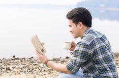 Manlig läsning en bok i parkera på en sommardag, kaffe royaltyfria bilder