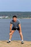 Manlig löpare som gör sträcka övningen som förbereder sig för morgongenomkörare i parkera Arkivbild