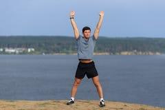 Manlig löpare som gör sträcka övningen som förbereder sig för morgongenomkörare i parkera Arkivfoto