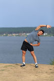 Manlig löpare som gör sträcka övningen som förbereder sig för morgongenomkörare i parkera Fotografering för Bildbyråer