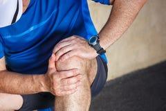 Manlig löpare som har problem i knä arkivfoton