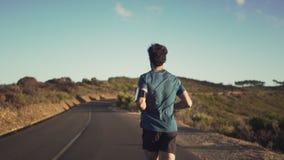 Manlig löpare som kör på vägen arkivfilmer