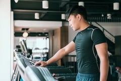 Manlig löpareaktiveringstrampkvarn i idrottshall arkivbilder