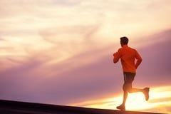 Manlig löparekontur som kör in i solnedgång Arkivbild