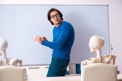 Manlig l?rare och skelett- student i klassrumet arkivbilder