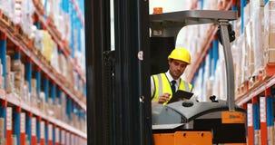 Manlig lagerarbetare som använder den digitala minnestavlan lager videofilmer