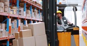 Manlig lagerarbetare som använder gaffeltrucken för lyftande materiel stock video