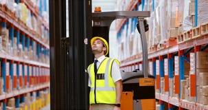 Manlig lagerarbetare som kontrollerar materielet för sändning lager videofilmer