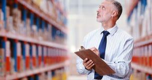 Manlig lagerarbetare som räknar materiel, och hållande på skrivplattan arkivfilmer