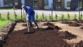 Manlig landscaper i arbetskläder att förbereda jordjord för att kärna ur för gräsmatta Statisk elektricitetskott arkivfilmer