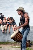 Manlig Latino percussionist som framme spelar rytm med hans djembevalsbongo av åhörarna på den Tam Tams festivalen royaltyfri fotografi