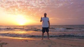 Manlig le turist som ser soluppgång och visar tummen upp på kusten lager videofilmer