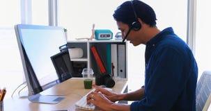 Manlig ledare i hörlurar med mikrofon som arbetar över datoren på hans skrivbord 4k stock video