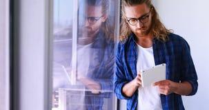 Manlig ledare som använder den digitala minnestavlan nära fönster arkivfilmer