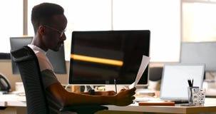 Manlig ledare som kontrollerar dokumentet på skrivbordet 4k lager videofilmer