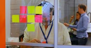 Manlig ledare som talar på hörlurar med mikrofonstund genom att använda den digitala minnestavlan 4k lager videofilmer