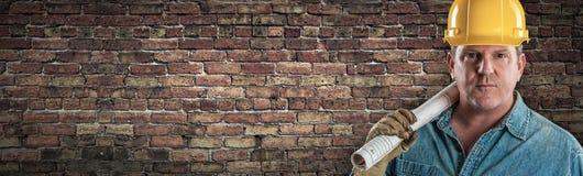 Manlig leverantör i den hårda hatten som rymmer konstruktionsplan i det Front Of Old Brick Wall banret med kopieringsutrymme royaltyfri fotografi