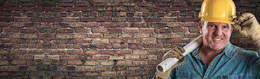 Manlig leverantör i den hårda hatten som rymmer konstruktionsplan i det Front Of Old Brick Wall banret med kopieringsutrymme arkivfoto