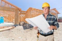 Manlig leverantör med husplan som framme bär den hårda hatten av Ne Royaltyfri Fotografi