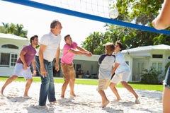 Manlig mång- utvecklingsfamilj som spelar volleyboll i trädgård Royaltyfri Bild