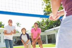 Manlig mång- utvecklingsfamilj som spelar volleyboll i trädgård Royaltyfri Foto