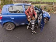 Manlig manpensionär för gamling som går till bilen med handikappRÖRLIGHET LÄTTVIKTS- ROLLATOR som VIKER TRI FOTGÄNGAREN som GÅR R Royaltyfri Foto