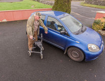 Manlig manpensionär för gamling som går till bilen med handikappRÖRLIGHET LÄTTVIKTS- ROLLATOR som VIKER TRI FOTGÄNGAREN som GÅR R Arkivfoto