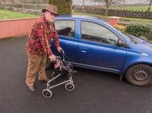 Manlig manpensionär för gamling som går till bilen med handikappRÖRLIGHET LÄTTVIKTS- ROLLATOR som VIKER TRI FOTGÄNGAREN som GÅR R Royaltyfria Foton
