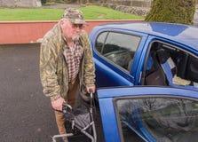 Manlig manpensionär för gamling som går till bilen med handikappRÖRLIGHET LÄTTVIKTS- ROLLATOR som VIKER TRI FOTGÄNGAREN som GÅR R Arkivbilder