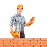 Manlig manuell arbetare med hjälmen som rymmer en tegelsten bak en tegelstenwa Arkivbilder