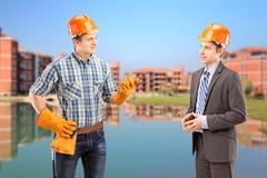 Manlig manuell arbetare som har en konversation med arkitekten, constru fotografering för bildbyråer