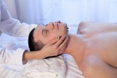 Manlig massör som gör vård- brunnsorttillvägagångssätt för massage Royaltyfria Bilder