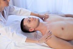 Manlig massör som gör vård- brunnsorttillvägagångssätt för massage Arkivbild
