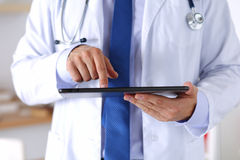 Manlig medicindoktor som rymmer digital minnestavlaPC royaltyfria foton