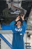 Manlig mekaniker Examining Exhaust System av bilen arkivfoto