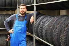 Manlig mekaniker med bilgummihjul Arkivfoto