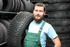 Manlig mekaniker med bilgummihjulet Arkivfoto