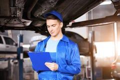 Manlig mekaniker med den undersökande bilen för skrivplatta i servicemitt royaltyfri bild