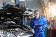 Manlig mekaniker med skrivplattan nära bilen i servicemitt arkivfoto