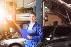 Manlig mekaniker med skrivplattan nära bilen i servicemitt royaltyfri fotografi