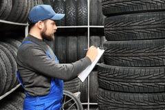 Manlig mekaniker med skrivplattan nära bilgummihjul Fotografering för Bildbyråer