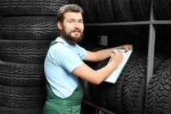 Manlig mekaniker med skrivplattan nära bilgummihjul Royaltyfri Foto