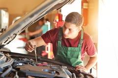 Manlig mekaniker som jämnt kontrollerar av olja i bilmotor royaltyfri bild