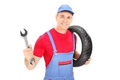 Manlig mekaniker som rymmer en skiftnyckel och ett gummihjul arkivfoto