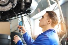 Manlig mekaniker som smörjer bilen i servicemitt arkivfoton