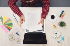 Manlig modedesginer som arbetar på skrivbordet med modesktech Överkant v arkivfoton