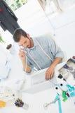 Manlig modeformgivare som använder bärbara datorn och telefonen i studio royaltyfri bild