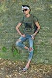 Manlig modell för överdådig hipster med solglasögon och en vit halsdukbenägenhet mot väggen arkivbilder