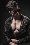 Manlig modell för härlig idrotts- kroppsbyggare som poserar i studio Uttryck på kamera Brutal man i läderdräkt Arkivfoto